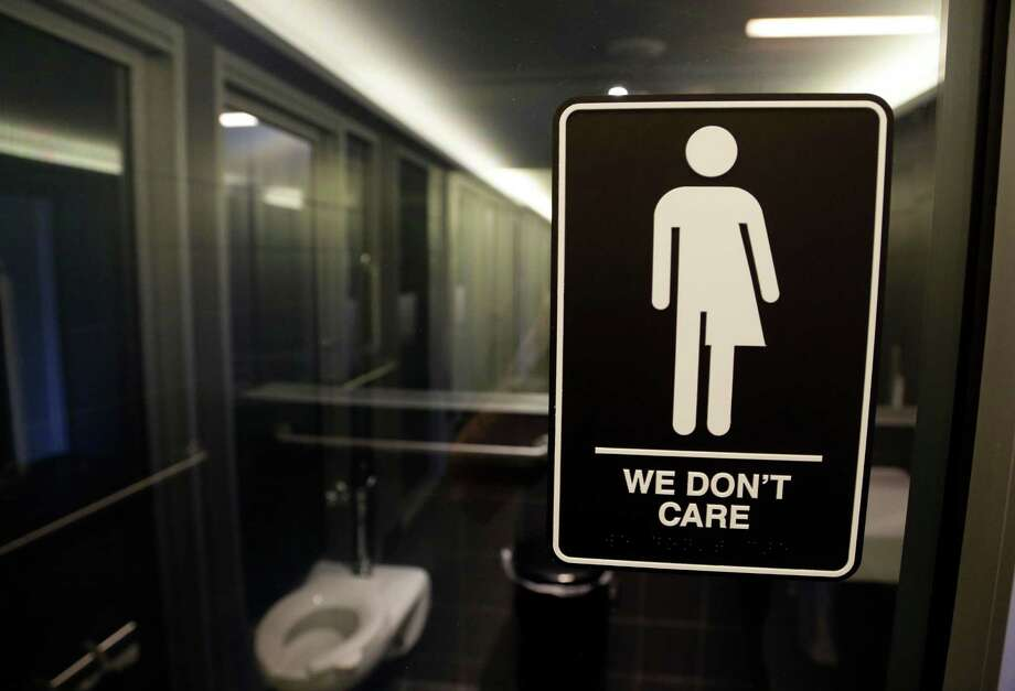 FILE - This Thursday, May 12, 2016, file photo, shows signage outside a restroom at 21c Museum Hotel in Durham, N.C. North Carolina is in a legal battle over a state law that requires transgender people to use the public restroom matching the sex on their birth certificate. Some small business owners already working to make their companies more welcoming to LGBT employees say the massacre at a gay dance club in Orlando, Fla., gives them an impetus to make more changes. In this photo, the Americans with Disabilities Act-compliant bathroom sign was designed by artist Peregrine Honig. (AP Photo/Gerry Broome, File) Photo: Gerry Broome, STF / AP
