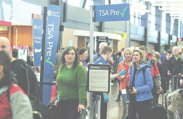 FILE - In this March 17, 2016, file photo, travelers authorized to use the Transportation Security Administration's PreCheck expedited security line at Seattle-Tacoma International Airport in Seattle have their documents checked by TSA workers. Thousands of fliers enrolled in trusted traveler programs such as PreCheck aren?t getting the expedited screening they paid for because of clerical errors with their reservations. (AP Photo/Ted S. Warren, File)