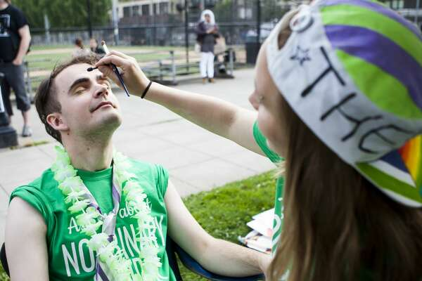 Adriaan Dippenaar brushes rainbow-themed eye shadow onto Richard McGovern at Cal Anderson Park in downtown Seattle during the Trans Pride events on June 24, 2016. (Lacey Young, seattlepi.com)