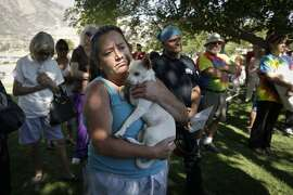 Evacuee Kimberly Tieche holds her 10-month old puppy while listening to the briefing on a wildfire at an evacuation center, Saturday, June 25, 2016, near Kernville, Calif. Tieche whose home was devastated by the wildfire said she only had five minutes to get out. (AP Photo/Jae C. Hong)