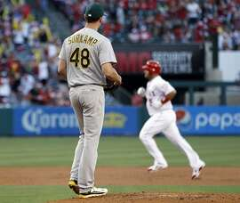 Oakland Athletics starting pitcher Eric Surkamp, left, watches as Los Angeles Angels designated hitter Albert Pujols, right, rounds the bases after hitting a two-run home run during the first inning of a baseball game in Anaheim, Calif., Friday, June 24, 2016. (AP Photo/Alex Gallardo)