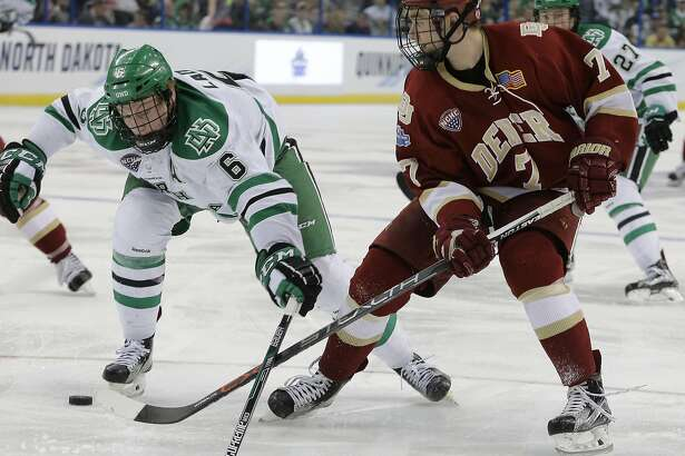 North Dakota defenseman Paul LaDue (6) knocks the puck away from Denver forward Dylan Gambrell during the second period of an NCAA Frozen Four semifinal college hockey game Thursday, April 7, 2016, in Tampa, Fla. (AP Photo/Chris O'Meara)