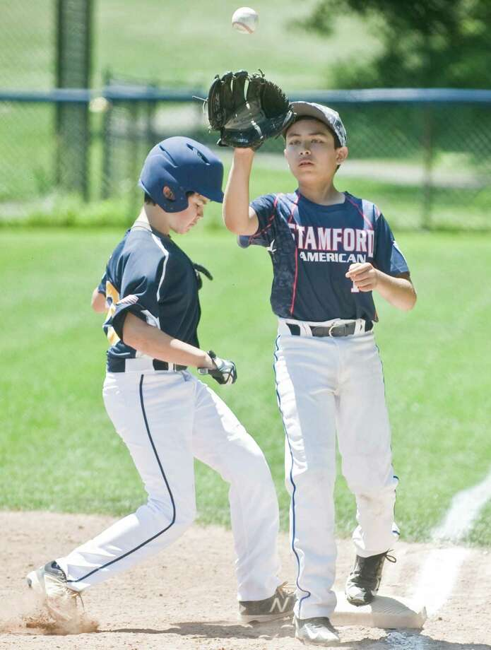 Weston's Tim Bello slips back to first as Stamford American's Mike Ajila takes the pick-off throw in the District 1 Little League game at Stamford. Saturday, June 25, 2016 Photo: Scott Mullin / For The / The News-Times Freelance