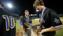 Alamo Heights' Morgan Dawley looks at the runner-up trophy with Jered Aldaz (22) and Michael Kelleher (10) after their team fell to Grapevine 9-2 during the UIL state baseball 5A championship in Round Rock on June 10, 2016.