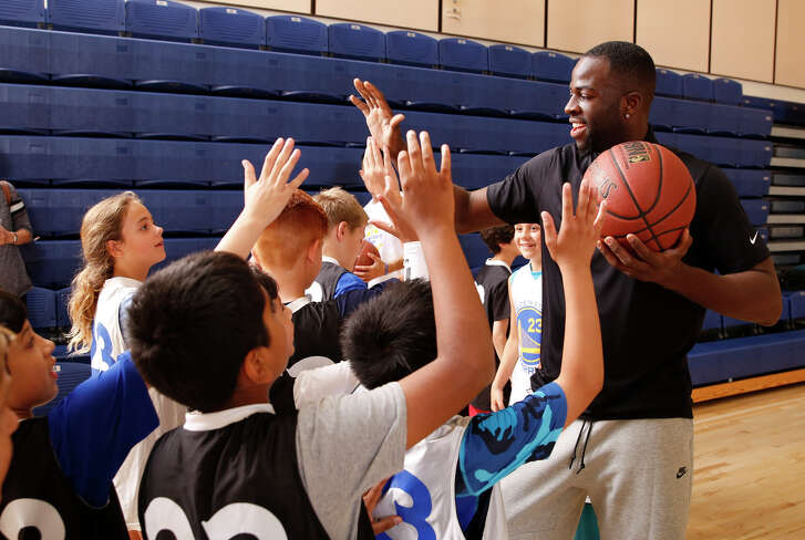 Draymond Green high-fives kids at his basketball camp at Cal State Monterey Bay. The 160 spots for the overnight camp sold out in about 35 minutes.