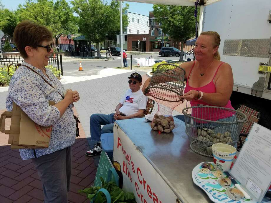 Customer Denise Augusewicz buys Little Neck clams from Laurie Popadic at the Danbury Farmers Market on Sat., June 25, 2016. Popadic owns Pepe's Cream of the Crop Shellfish Farm. Photo: Alex Wolff / Hearst Connecticut Media