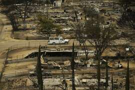 A pickup truck passes by the remains of mobile homes devastated by a wildfire, Saturday, June 25, 2016, in South Lake, Calif.  Gov. Jerry Brown declared a state of emergency, freeing up money and resources to fight the fire and to clean up in the aftermath. The Federal Emergency Management Agency also authorized the use of funds for firefighting efforts. (AP Photo/Jae C. Hong)