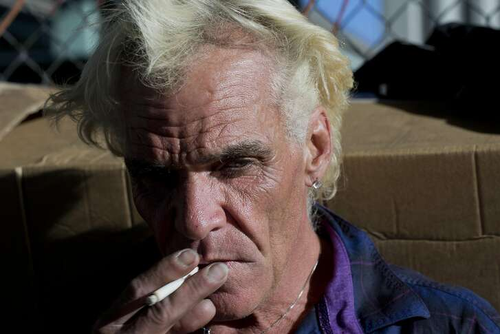 """J.C. Pearson II smokes a cigarette on the sidewalk where he lives in the Design District of San Francisco on Wednesday, June 15, 2016. A hairstylist, he's been cutting hair for people at Martin de Porres House of Hospitality for around 18 years. """"If you can�t save yourself, help save the world,"""" he said."""