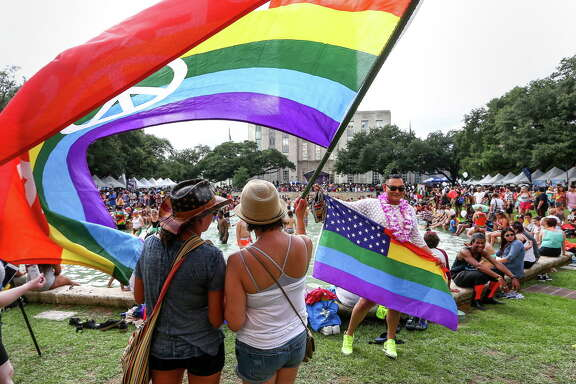 "Rocio Castillo, right, and her friend ""Carol,"" stand under a rainbow flag in Hermann Square as they celebrate the 2016 Houston Pride Festival, Saturday, June 25, 2016, in Houston. ""It's very special because Orlando touched my heart,"" Castillo said."