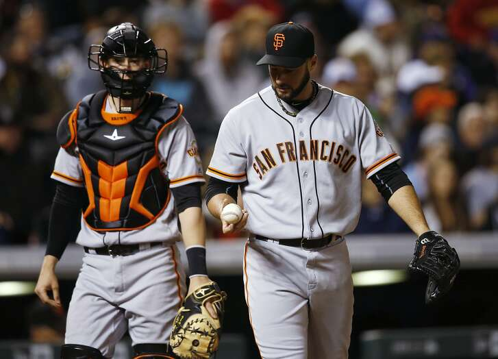 San Francisco Giants relief pitcher George Kontos, right, looks over the ball next to catcher Trevor Brown fter Kontos gave up an RBI single to Colorado Rockies' Tony Wolters during the eighth inning of a baseball game Friday, May 27, 2016, in Denver. Colorado won 5-2. (AP Photo/David Zalubowski)