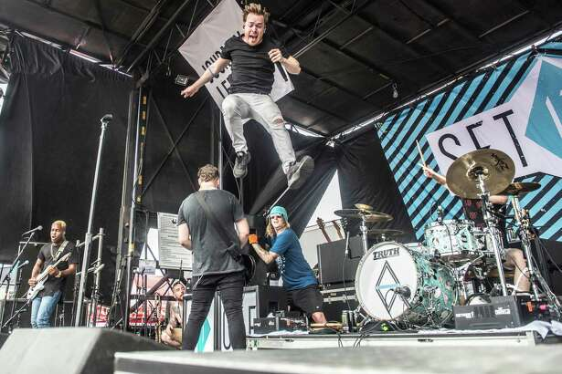 Set It Off lead singer Cody Carson leaps from a speaker at the Warped Tour at the AT&T Center.