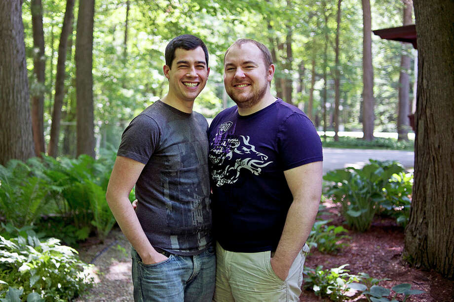 ERIN KIRKLAND | ekirkland@mdn.net  Kyle Gordon, left, and his husband Brad Bidwell, right, pose for a portrait on Friday outside their Larkin Township home. The couple was married in Canada in 2014, but were not recognized in the United States until the Supreme Court legalized gay marriage one year ago. The two, who are originally from the area, did not meet until attending school at Wayne State University. / Midland Daily News