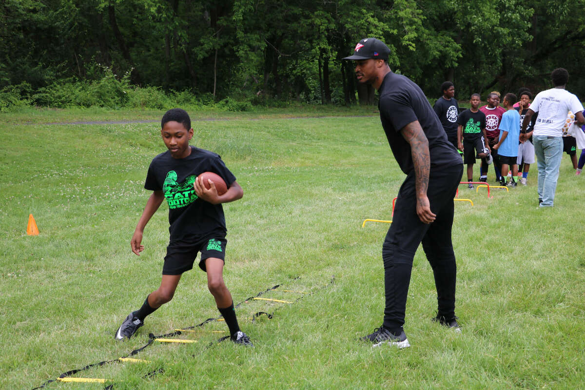 Jaelen Strong teaches one of his students at his annual football camp in Philadelphia.