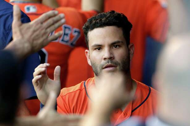 Houston Astros Jose Altuve is congratulated in the dugout after scoring from third base in the fourth inning of a baseball game against the Kansas City Royals at Kauffman Stadium in Kansas City, Mo., Saturday, June 25, 2016. (AP Photo/Colin E. Braley)