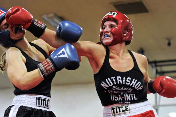 Sarah Bell, right, from Danbury's Champs Boxing, and Jennifer Diggs, from S.E.T. Gym, fight in a 152 lbs bout in the Summer Sizzler amateur boxing event at the Danbury War Memorial on Saturday night, June 25, 2016, in Danbury, Conn.