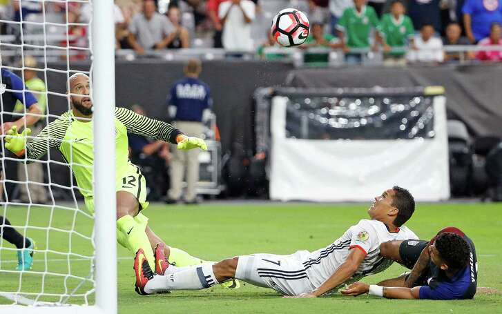 Colombia's Carlos Bacca, center, sends the ball past U.S. goalie Tim Howard, left, for the game's only goal despite the efforts of defender DeAndre Yedlin.
