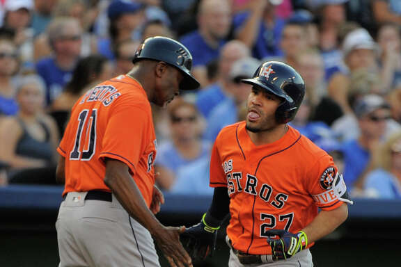 Astros second baseman Jose Altuve, left, rounds third to a celebratory greeting from coach Gary Pettis after Altuve's three-run homer in the second. Royals starter Chris Young, above, has the opposite feeling after allowing a solo home run to the next batter, Carlos Correa. The Astros' seven-run second helped them score 13 runs for a second consecutive game.