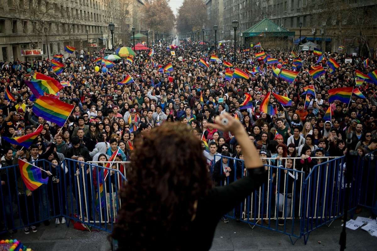 Pride celebrations around the world 2016: People watch a singer perform during the 16th annual gay pride celebrations to mark the upcoming International Gay Pride Day, and to honor the victims of the Orlando nightclub shooting, in Santiago, Chile, Saturday, June 25, 2016. Marchers are also demanding laws in favor of same-sex marriage and gender identity.