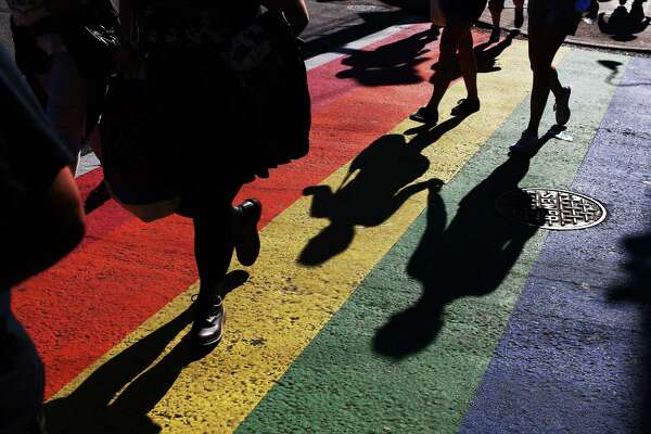 Two people hold hands as they walk over a rainbow crosswalk on E Pike Street in Capitol Hill during Seattle PrideFest, June 25, 2016.