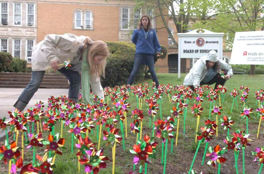 KIds in Crisis Youth Corps members Marina Milos, 17, of Greenwich, left, Adrianna Baker, 17, of Darien, and Dannie Forte, also of Darien, 18, plant 1,531 colorful metallic pinwheels, representing the children who have been abused this year, at the grounds of the Greenwich Board of Education, on Sunday, April 25, 2010. Photo: Helen Neafsey / Greenwich Time
