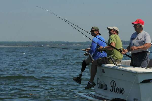 Sergio Cano of Seymour, Conn, a wounded combat veteran looks over as his father Walter Cano, center, attempts to hook a strike while fishing with Joseph Santagata on the Long Island Sound off of Stamford, Connecticut. The group was participating in the Hooks for Heroes Charity Fishing Tournament, hosted by the Halloween Yacht Club in Stamford, Conn. on Saturday, June 25, 2016. The event brought together area Veterans and several injured Vets from the Walter Reed Army Hospital for a day of fishing on the Long Island Sound. Several thousands of dollars were raised to help benefit Operation Gift Cards, one of several charity's supporting combat wounded vets.