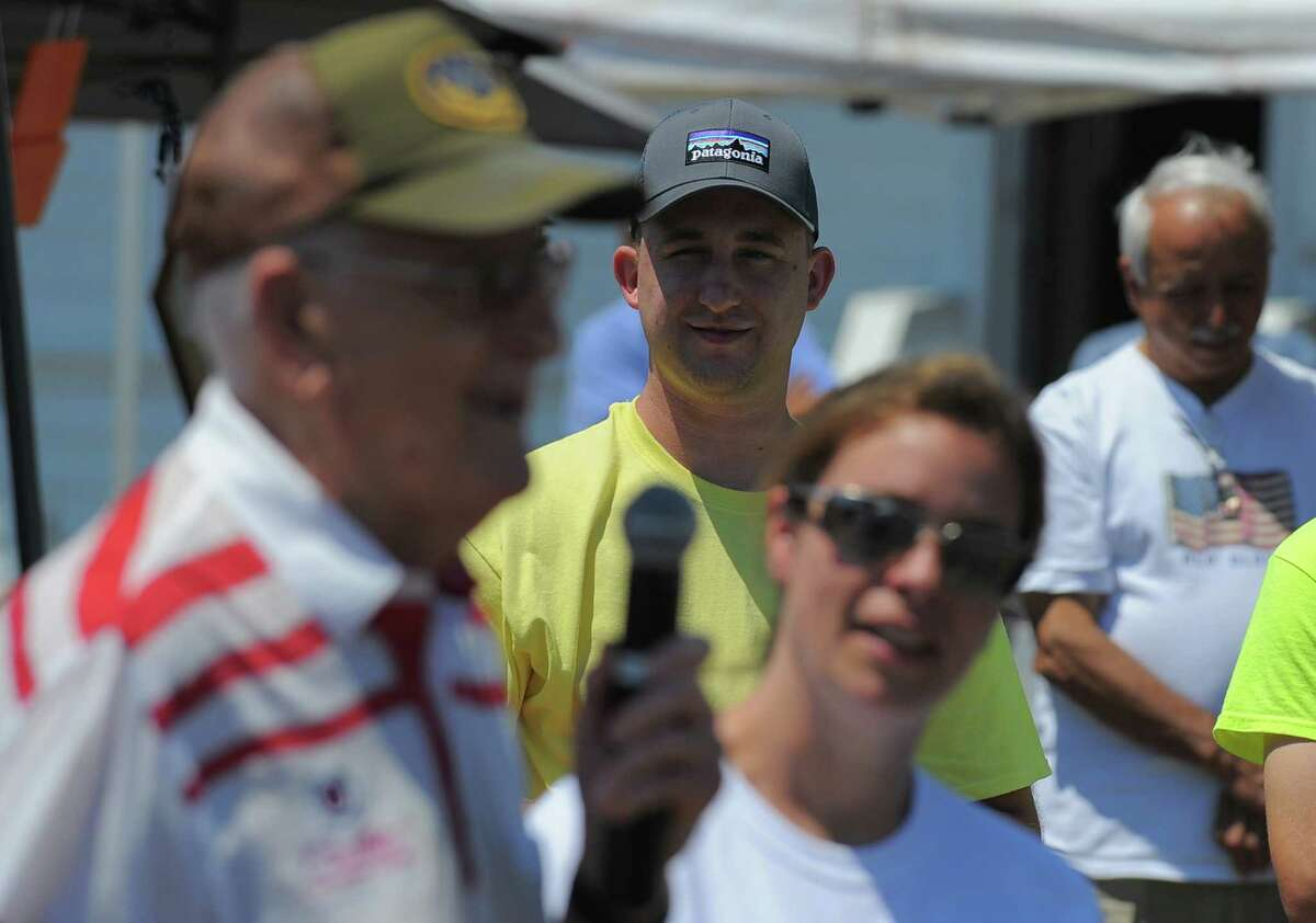 Adam Avenia, one of several Wounded Heroes participating in the Hooks for Heroes Charity Fishing Tournament at the Halloween Yacht Club in Stamford, Conn. on Saturday, June 25, 2016, listens as Retired Brigadier General Monsignor Thaddeus F. Malanowski offers a prayer. The event brought together area Veterans and several injured Vets from the Walter Reed Army Hospital for a day of fishing on the Long Island Sound. Several thousands of dollars were raised to help benefit Operation Gift Cards, one of several charity's supporting combat wounded vets.