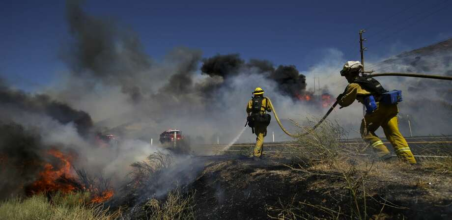 Firefighters put out a spot fire as they continue to battle a wildfire burning along Highway 178 near Lake Isabella, Calif., Friday, June 24, 2016. The wildfire that roared across dry brush and trees in the mountains of central California gave residents little time to flee as flames burned homes to the ground, propane tanks exploded and smoke obscured the path to safety. (AP Photo/Jae C. Hong) Photo: Jae C. Hong/AP
