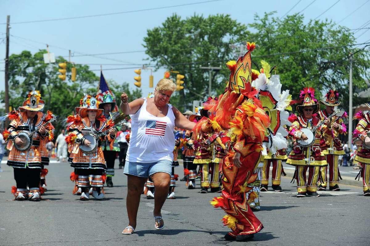 Linda Hooker, of Stratford, joins the Uptown String Band in dancing during the 68th annual Barnum Festival Great Street Parade in Bridgeport, Conn. on Sunday, June 26, 2016.