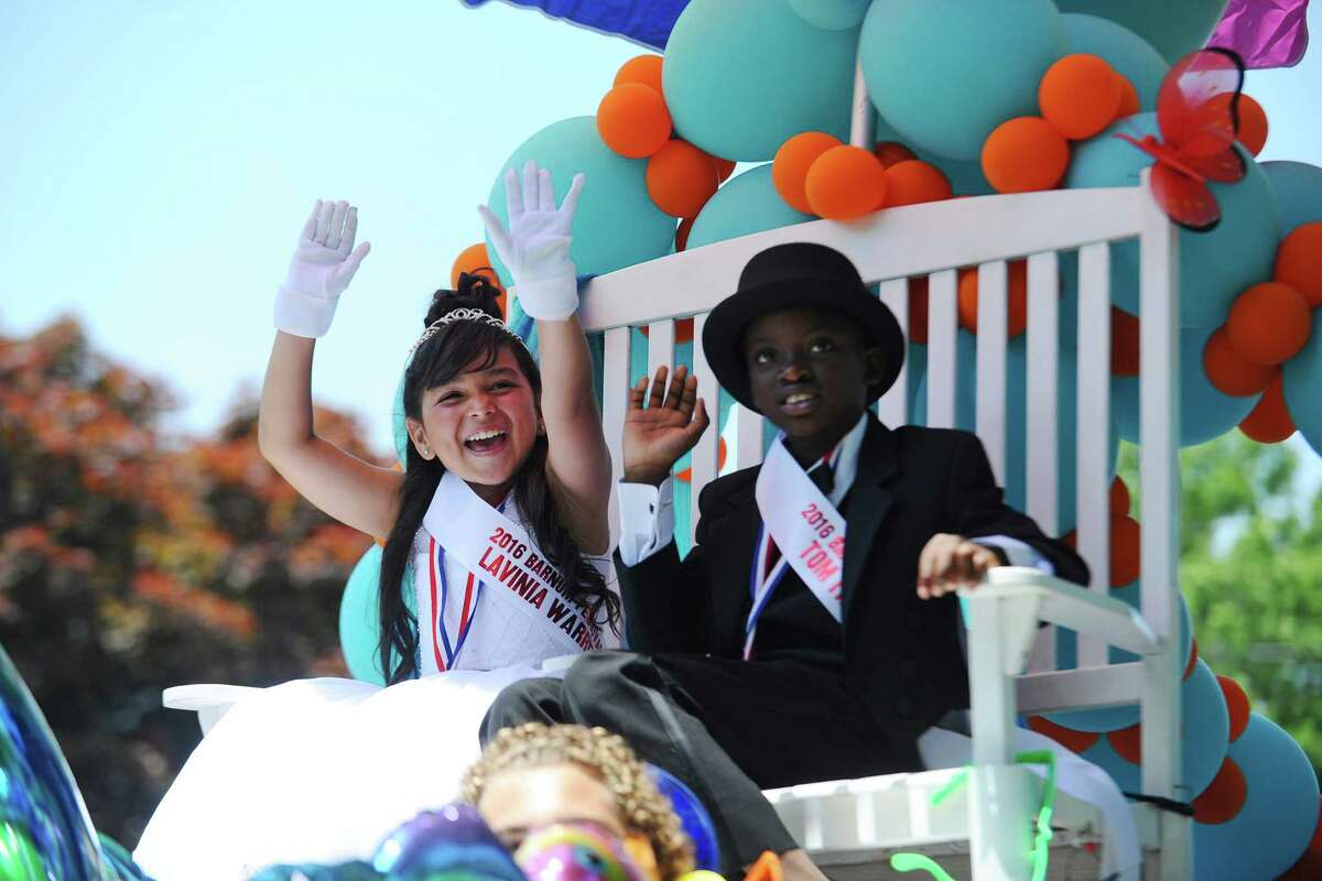 Sofia Atehortua, left, and Malcolm Dennis wave to the crowd during the 68th annual Barnum Festival Great Street Parade in Bridgeport, Conn. on Sunday, June 26, 2016.