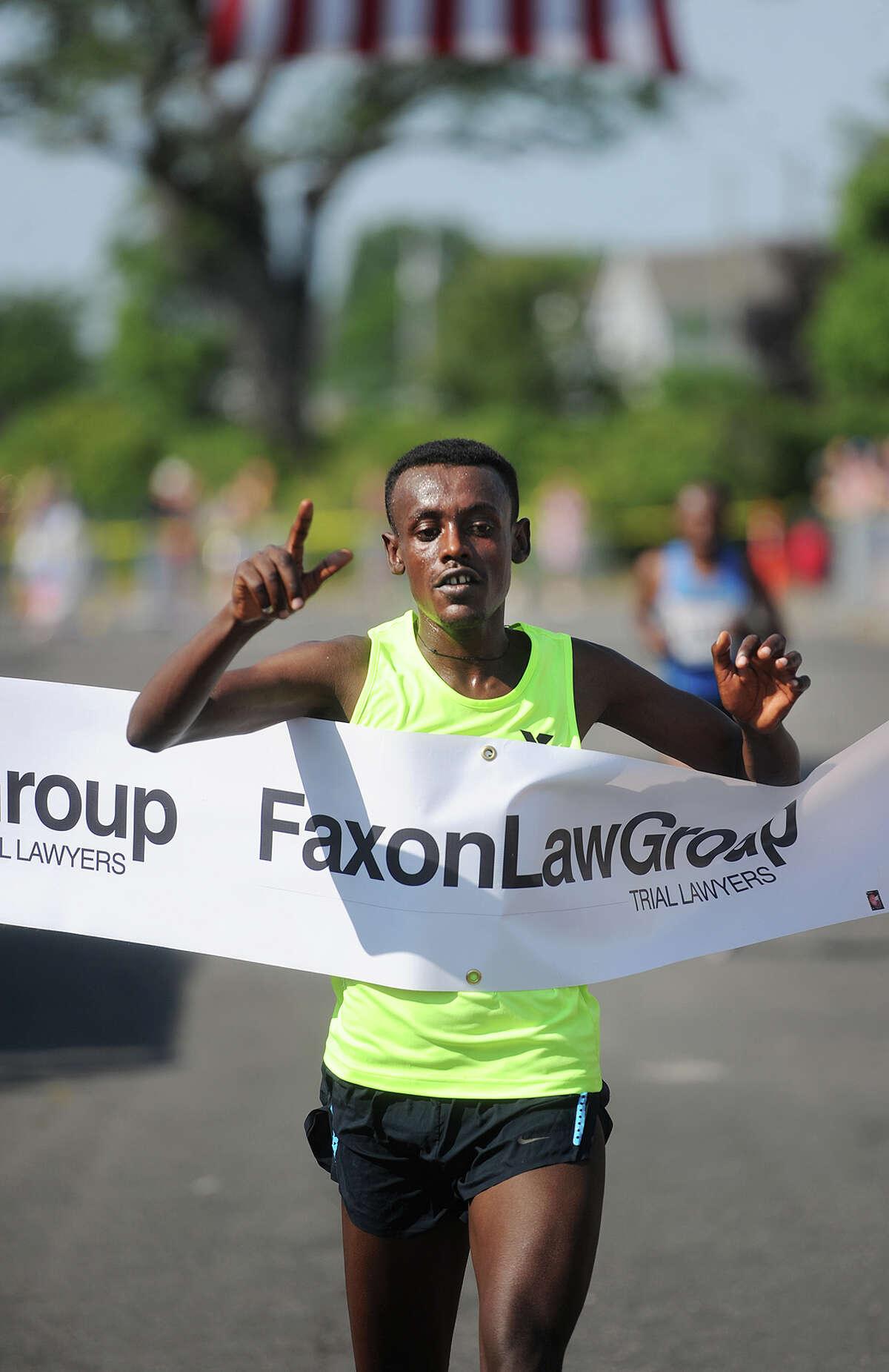 Ethiopian Tsegaye Getachw breaks the tape to win the 2016 Faxon Law Fairfield Half Marathon in Fairfield, Conn. on Sunday, June 26, 2016.