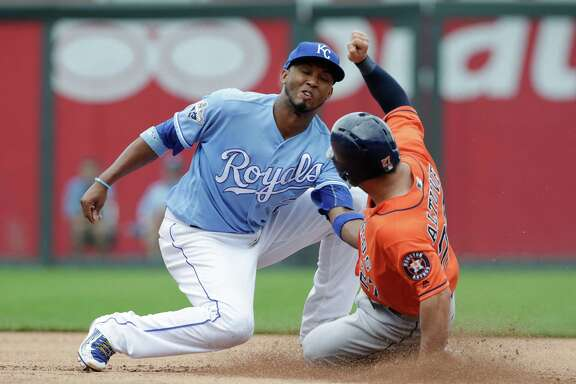 Houston Astros' Jose Altuve (27) is tagged out attempting to steal second base by Kansas City Royals shortstop Alcides Escobar (2) in the fourth inning of a baseball game at Kauffman Stadium in Kansas City, Mo., Sunday, June 26, 2016. (AP Photo/Colin E. Braley)