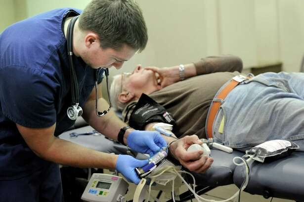 Chris Banziruk, 26, of Oxford, Conn., a phlebotomist with the American Red Cross draws blood from Harry Doyle, 76, of Danbury Saturday, January 24, 2015. The American Red Cross urges eligible donors to give blood in the weeks surrounding Independence Day to help ensure a sufficient blood supply for patients now and throughout the summer.