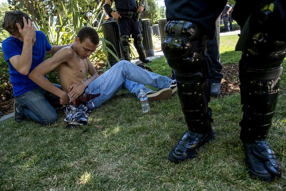 Sean Moore, 23, of Sacramento waits for medics with a friends after being stabbed by protesters at the State Capitol in Sacramento, Calif., on Sunday, June 26, 2016. Sacramento Fire Department spokesman Chris Harvey says a rally by KKK and other right-wing extremists groups turned violent Sunday when they were met by counterprotesters. (Renee C. Byer/The Sacramento Bee via AP)  MAGS OUT; LOCAL TELEVISION OUT (KCRA3, KXTV10, KOVR13, KUVS19, KMAZ31, KTXL40); MANDATORY CREDIT Photo: Renee C. Byer, Associated Press