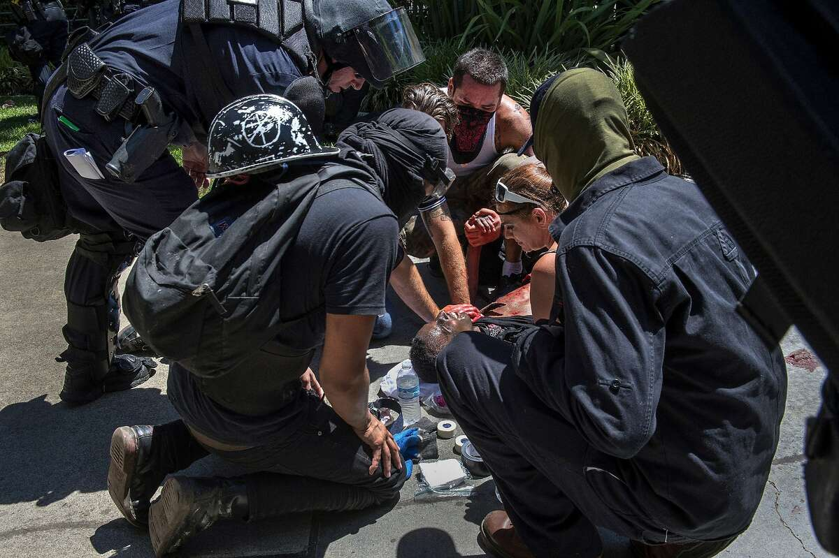 A victim is attended after he was stabbed during a rally at the State Capitol in Sacramento, Calif., on Sunday, June 26, 2016. Sacramento Fire Department spokesman Chris Harvey says a rally by KKK and other right-wing extremists groups turned violent Sunday when they were met by counterprotesters. (Rene C. Byer/The Sacramento Bee via AP) MAGS OUT; LOCAL TELEVISION OUT (KCRA3, KXTV10, KOVR13, KUVS19, KMAZ31, KTXL40); MANDATORY CREDIT