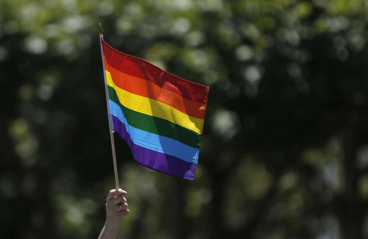 A PRide attendee raises a Rainbow flag at Civic Center Plaza as thousands gathered to celebrate San Francisco Pride in San Francisco, Calif., on Sunday, June 26, 2016.