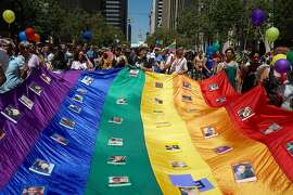 Members of Decolores carry a flag with photos of the Orlando shooting victims during the annual Pride Parade in downtown San Francisco on Sunday, June 26, 2016. The theme for the parade this year is For Racial and Economic Justice.