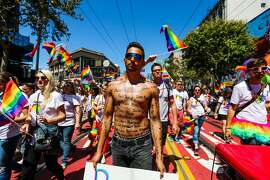 Thomas Pedrozza (center), bears the name of all of the Orlando victims across his body, as he walks in the 46th annual LGBT Pride Parade, in San Francisco, California, on Sunday, June 26, 2016.