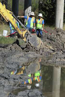 San Antonio Water System workers direct heavy equipment at the scene of a sewage spill Dec. 5, 2012, near Wurzbach Parkway and Weidner Road. SAWS reported that about 63,000 gallons of sewage leaked.