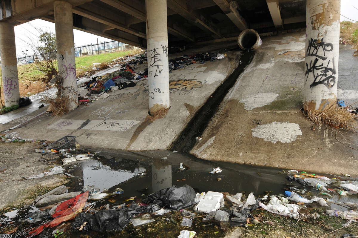 Water flows out of a storm drain under the Brazos Street bridge near a person who is homeless.