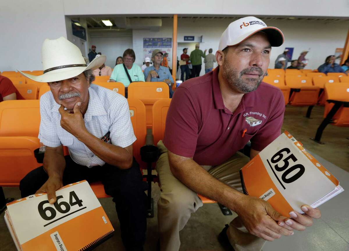 S. Luzno Torres, left, and Hector M. Ramon, right, both of Katy wait to make a bid during an auction at Ritchie Bros. Auctioneers, 15500 Eastex Freeway, Wednesday, June 22, 2016, in Humble.