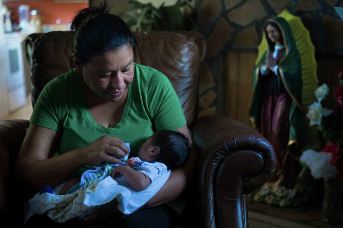 Leticia Sosa, holds her sixth and final baby, a three-week-old son Martin Aurelio Sosa at her home in Alvin, Thursday, June 23, 2016. Sosa expressed frustration and disappointment about the U.S. Supreme Court 4-to4 decision that allows a lower court ruling to stand which would not provide temporary work permits to parents of Americans and lawful permanent residents. For Leticia, the future of her family is uncertain because of her undocumented status. Five of Leticia Sosa's children are American citizens.