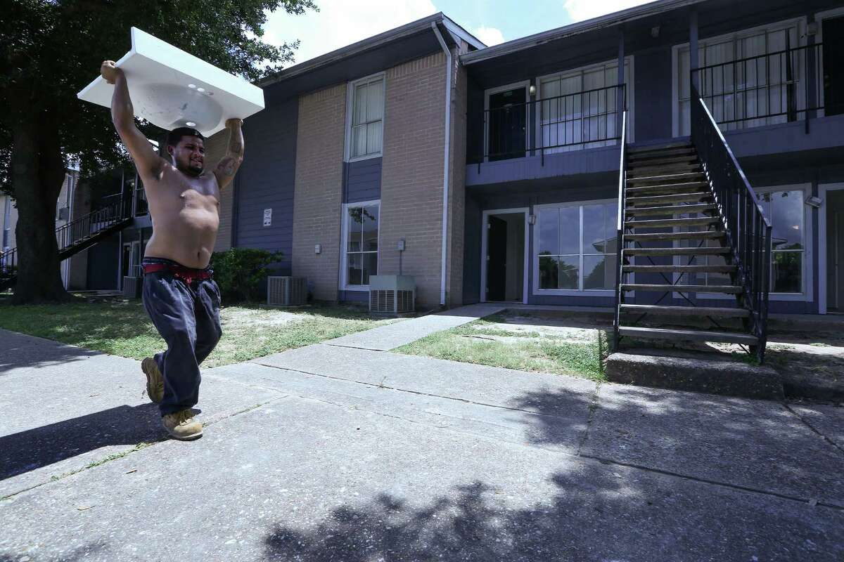 Contractor Steven Nava carries a sink into a Arbor Court apartment, federally subsidized housing.