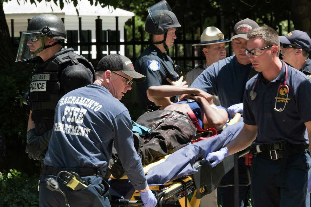Paramedics rush a stabbing victim away Sunday out-side the state Capitol building in Sacramento, Calif.
