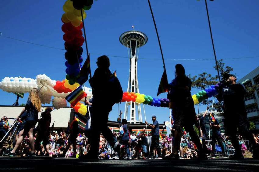 2016: The Space Needle watches over as the 42nd annual Seattle Pride Parade passes beneath on Denny Way, Sunday, June 26, 2016.