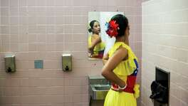 Beth Mendez, 38, of Atlanta adjusts her dress before performing a Venezuelan folk dance during a festival and fundraiser on Saturday at at O.P. Schanbel Park in San Antonio. It celebrated Venezuelan culture and raised money to help Venezuelan people suffering from food shortages, extreme inflation and political turmoil.