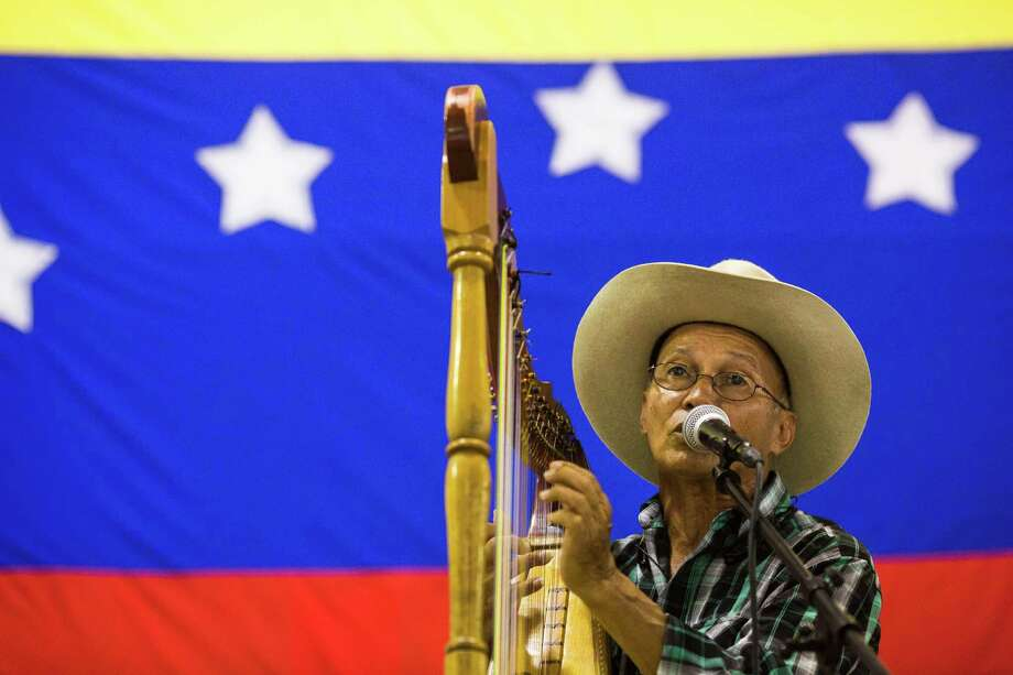 Singing and playing the harp at O.P. Schanbel Park, Rene Devia, of Colombia, plays the South American harp during a festival to raise money to aid victims of the economic and political hardship in Venezuela. A reader says those hardships were caused by the socialist regime in that country. Photo: BRITTANY GREESON /San Antonio Express-News / © 2015 San Antonio Express-News