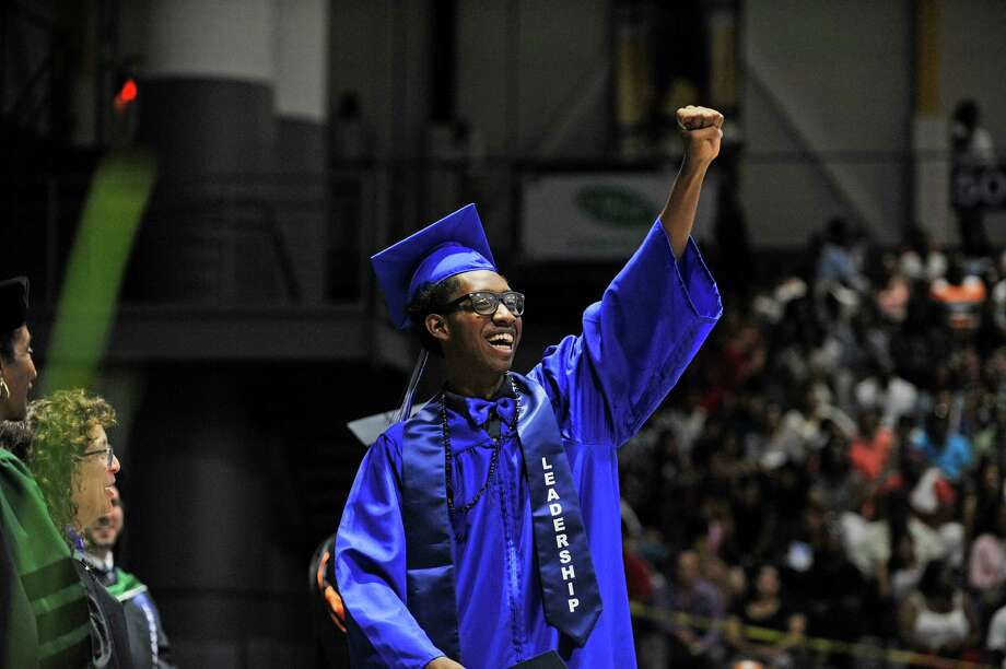 Albany High School graduate, DiJour Carter, waves to the crowd as he walks across the stage after receiving a scholarship during the graduation  ceremony inside the SEFCU Arena on Sunday, June 26, 2016, in Albany, N.Y.  This year the school graduated 480 students.  (Paul Buckowski / Times Union) Photo: PAUL BUCKOWSKI / 20036735A