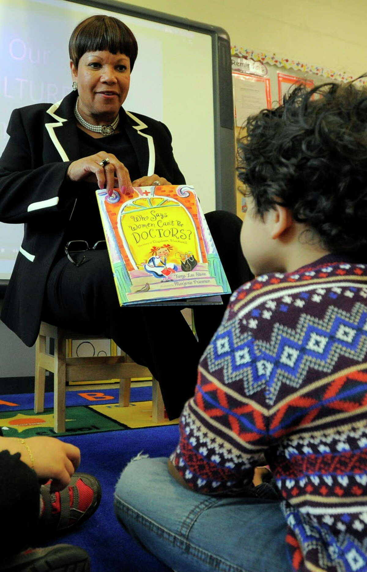 """Mary Jennings, Director of Early Childhood Development and Intervention in Stamford Public Schools, reads """"Who Says Women Can't Be Doctors"""" to four-year-olds in the School Readiness Program at APPLE Early Childhood Education Center in Stamford on May 6, 2016. Jennings is retiring after 25 years with the district and 49 years in education."""