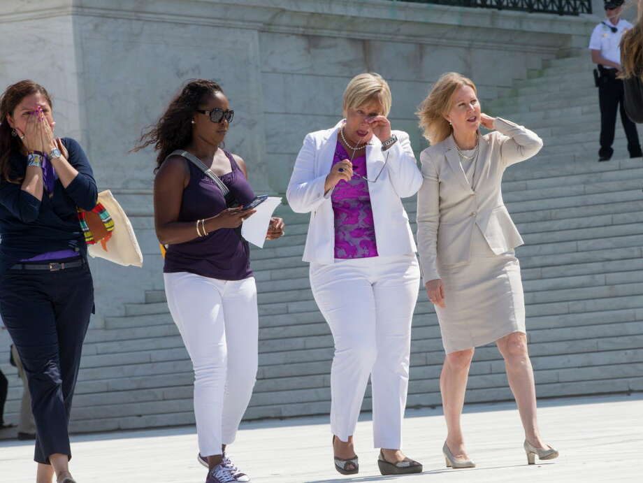 Amy Hagstrom Miller, second from right, founder of Whole Woman's Health, a Texas women's health clinic that provides abortions, leaves the Supreme Court in Washington, Monday, June 27, 2016, with Center for Reproductive Rights President Nancy Northup, far right, as the justices struck down the strict Texas anti-abortion restriction law known as HB2. The justices voted 5-3 in favor of Texas clinics that had argued the regulations were a thinly veiled attempt to make it harder for women to get an abortion in the nation's second-most populous state. The case is Whole Woman's Health v. Hellerstedt. (AP Photo/J. Scott Applewhite) Photo: J. Scott Applewhite, Associated Press / AP