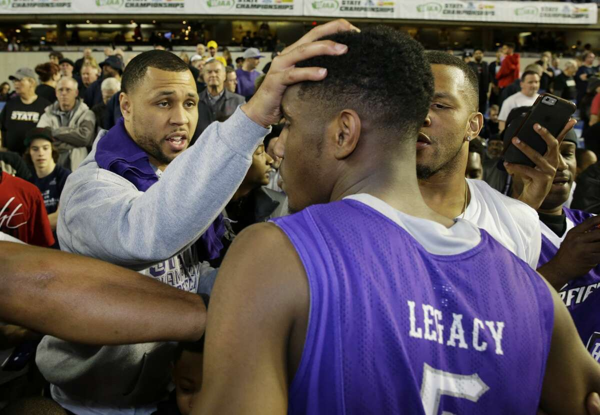 Former NBA basketball player and Garfield High School alumnus Brandon Roy, left, greets Garfield's Jaylen Nowell, center, after Nowell scored 23 points to lead Garfield to beat Rainier Beach 66-51 to win the boys 3A high school basketball championship, Saturday, March 7, 2015, in Tacoma, Wash. Roy was named the new head basketball coach at Seattle's Nathan Hale High School on Friday.